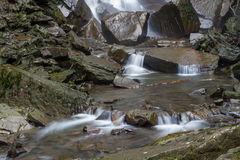 Water flowing over stones. By base of waterfall. Stock Photo