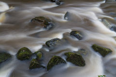 Water flowing over stones. near base of waterfall winter. Royalty Free Stock Images