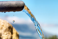 Water flowing from pipe against blurred mountains Royalty Free Stock Image