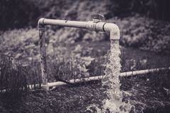 Water flowing through a pipe stock photo