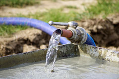 Water flowing from pipe to container Stock Images