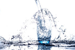 Water flowing and splashing into a glass Stock Images