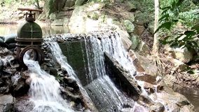 The water flowing from the steel drain into the brook of the waterfall in the tropical forest. The water flowing from the steel drain into the brook  of the stock video