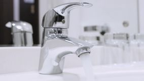 Water flowing from the tap stock video footage