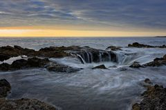 Water flowing into Thor`s Well during dramatic sunset Cape Perpetua Oregon