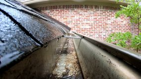 Water flowing thru gutter off shingled roof