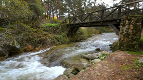 Water flowing under an ancient wood bridge in river Eresma at Boca del Asno natural park on a rainy day in Segovia, Spain. stock footage