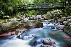 Water flowing under a bridge. Long exposure of a stream with water flowing under an old bridge and over rocks forming a shallow waterfall in a verdant green Stock Image