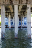 Water flowing under bridge. View from underneath concrete bridge of pylons and water moving south Stock Photography
