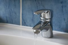 Water flowing from water tap in the bathroom. Water flowing from chrome water tap in the bathroom Royalty Free Stock Photo