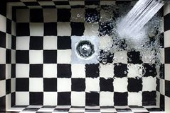 Water Flowing on White and Black Checked Bath Tub Royalty Free Stock Photos