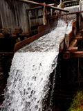 Water flows channeled into an wooden old mill.  stock photography