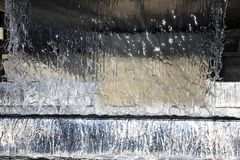 Water fountain with cascade and backlight. Water flows down the cascade waterfall Royalty Free Stock Image