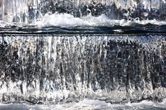 Water fountain with cascade and backlight. Water flows down the cascade waterfall Stock Photography