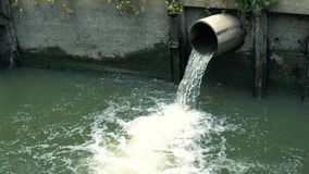 Water flows down from sewer pipe into drainage canal in the downtown