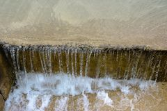 Water flows down on a step. A stream of water flows down the stairs stock images
