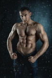Water flows on the embossed male body builder. Around the flying drops of water splashes on the body Stock Image