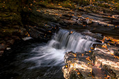 Water flows gently over rocks in Fall Royalty Free Stock Photos