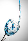 Water flows in a glass. Blue water flows in a wine-glass. In a glass from glass a wave Stock Images