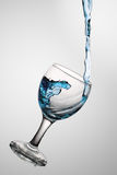 Water flows in a glass. Dark blue water flows in a wine-glass. In a glass from glass a wave Royalty Free Stock Image