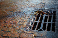 Water flows into the hatch on a spring sunny day. Melted water flows down through the manhole cover on a sunny spring day stock photos