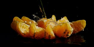Water flows into the interior of peeled orange. Orange lighted by the sun, and arranged in a star shape. Stream of water flows into the inside of the fruit and Stock Image