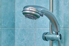 Water flows from shower head inside bathroom, fixed in holder. Water flows from the new shower head, which is fixed in the holder in the bathroom with blue Royalty Free Stock Images