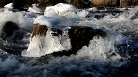 Water flows over the frozen rocks stock footage
