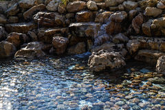 Water flows over the rocks into the pool with stones at the bottom Royalty Free Stock Photography