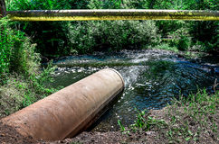 Water flows from the pipe into the river. Stock Photography