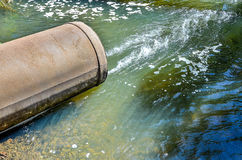 Water flows from the pipe into the river. Stock Photos