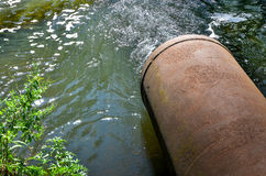 Water flows from the pipe into the river. Stock Image