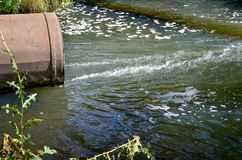 Water flows from the pipe into the river. Royalty Free Stock Image