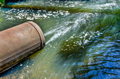 Water flows from the pipe into the river. Royalty Free Stock Photo