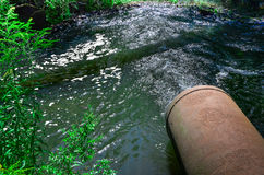 Water flows from the pipe into the river. Stock Photo