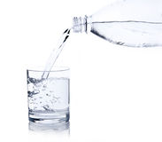 Water, flows from a plastic bottle in a glass Royalty Free Stock Photo
