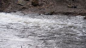 Water flows at the river bank stock video