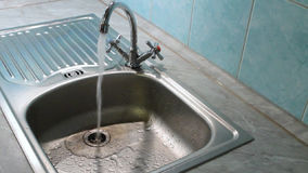 Water flows into the sink from the kitchen faucet stock footage