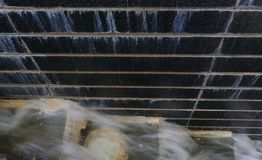Water flows from step to step. Blurred motion of water flows from step to step and black stone wall with water falls, top view image stock photography