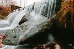 Water flows on stock pipes and follows in the wood. Royalty Free Stock Image