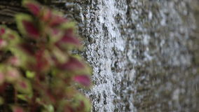 Water flows through stone wall Stock Photo