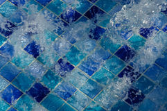 Water flows into the swimming pool with sunny reflections.  Royalty Free Stock Image