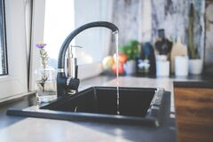 Water flows from the tap to sink Stock Photography