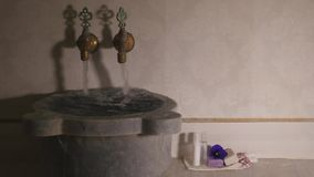 Water flowing from faucets and from marbel bowl in Turkish bath. Water flows from two faucets with cold and hot water and out of marble bowl in Turkish bath stock footage