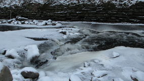 Water Flows under Ice on Minnehaha Creek. Water flowing under ice on a creek stock footage