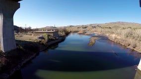 Water flows under an Idaho bridge stock footage