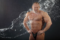 Water flows on undressed bodybuilder Royalty Free Stock Photo