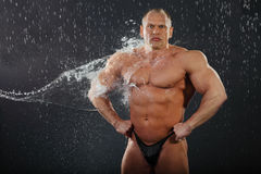 Water flows on undressed bodybuilder Royalty Free Stock Images