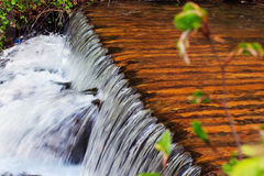 Water flows through the wooden logs, falling cascade down Royalty Free Stock Photos