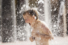 Water fountain. A boy playing with water in park fountain. Hot summer royalty free stock photography